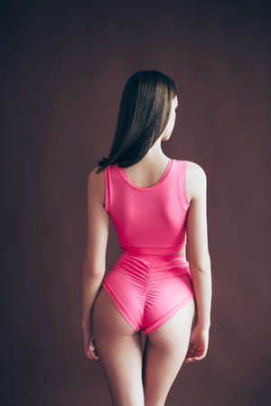 Back view of sexy young woman in swimsuit posing in studio. Beach, rest, sport, relax concept