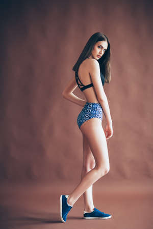 Full length portrait of young beautiful girl in sexy sportswear posing in studio. Sports style, fitness, shaping, fashion concept