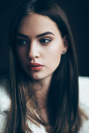 Young beautiful woman portrait, close-up. Pretty girl with red lipstick and stylish hairdo. Pensive look of the female model