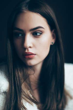 Portrait de jeune femme magnifique, gros plan. Jolie fille avec rouge à lèvres et une coiffure élégante. Regard pensif du modèle féminin