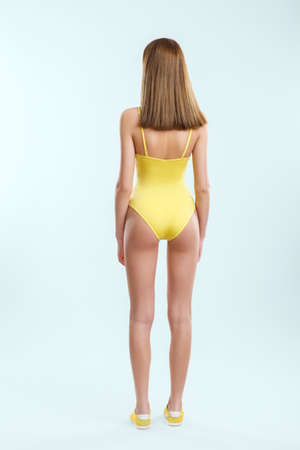 Rear view of beautiful young girl in yellow swimsuit and sneakers posing in studio.