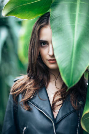 Fashion portrait of beautiful mysterious woman hide behind big leaf, close up. Girl with half closed face in greenhouse