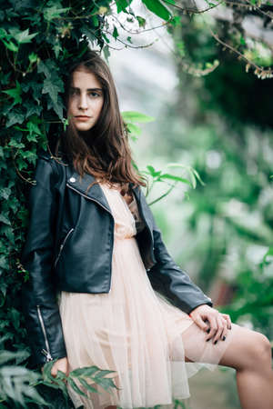 Fashion portrait of young stylish woman in pink dress and leather jacket posing on nature background. Beauty concept