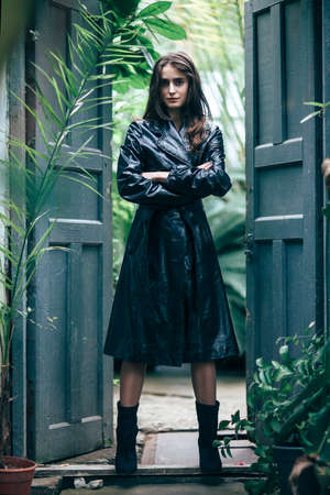 Fashion portrait of young beautiful girl in black stylish coat standing in doorway, hands crossed. Full length  Stock Photo