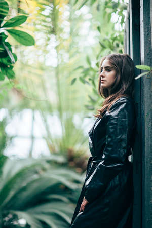 Profile portrait of young fashion woman in black jacket leaning back door jamb. Portrait on plants background.