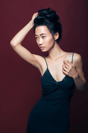 茶色の背景にスタジオでポーズ黒のドレスを着た美しいアジアの女性。プリティファッションモデルの肖像画 写真素材