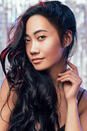 Portrait of cute eastern girl closeup. Young brunette with curly long hair elegantly posing, smiling and touching her neck with her finger Stock Photo