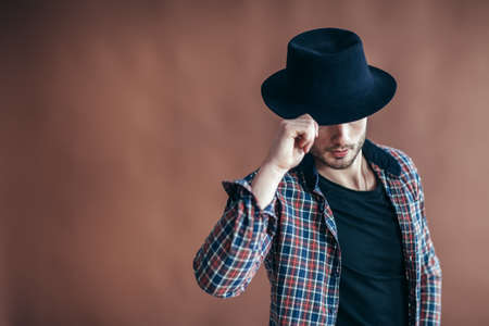 Young hipster man wearing hat posing on brown background with copy space