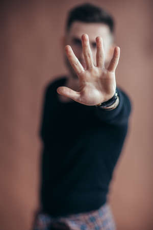 Portrait of young man doing stop hand sign on brown background Banco de Imagens - 100141739