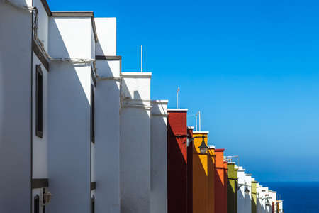Multicolored houses on island tenerife, side view. Colorful facades of buildings lined up in row under blue tropical sun