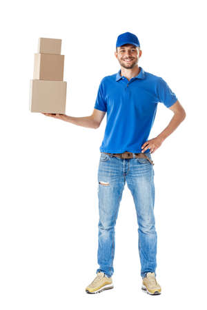 Full length portrait of smiling delivery man holding pile of cardboard boxes in one hand isolated on white background
