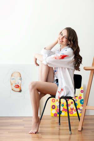 Beautiful happy female artist posing in her art studio. Creative concept Stock Photo
