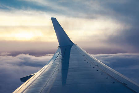 View of airplane wing from aircraft window on sunset time. Travel concept
