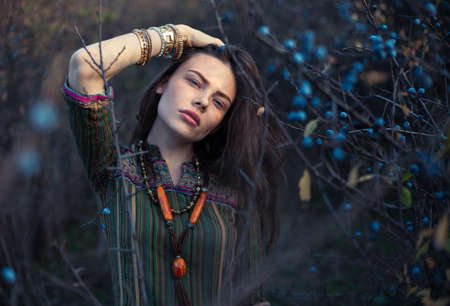 Fashion portrait of young hippie woman at sunset posing on nature background