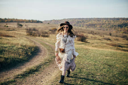 Beautiful young boho woman walking on nature. Freedom lifestyle