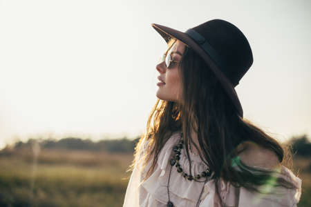 Side view portrait of young beautiful woman in hat with copy space on nature. boho, hipster fashion