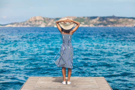 Happy woman in hat relaxing on sea pier in Sardinia island, Italy. Summer vacations concept 스톡 콘텐츠