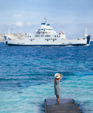 Beautiful young woman in hat relax on wooden pier on Sardinia beach, cruise ship on background Standard-Bild - 115809235