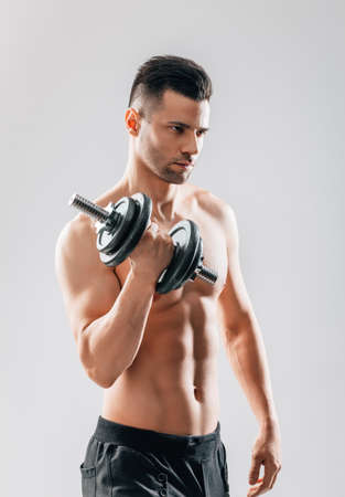 Muscular bodybuilder man doing exercises with dumbbell. Sport concept Фото со стока