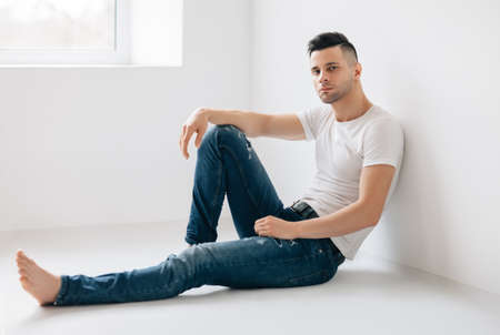 Thoughtful handsome man portrait sitting on floor. Male beauty concept Stock Photo
