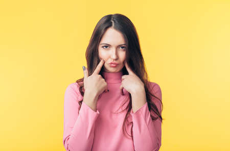 Displeased capricious woman grimacing isolated on yellow background
