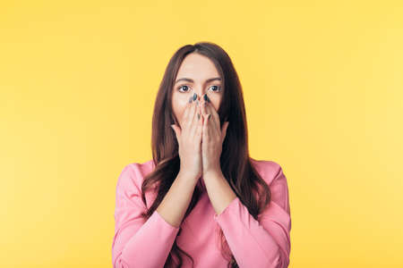 Shocked excited woman covering her mouth with hands isolated on yellow background