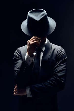 Man in pak verbergen gezicht achter zijn hoed geïsoleerd op donkere achtergrond. geheim en incognito concept