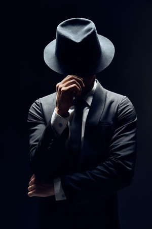 Man in suit hiding face behind his hat isolated on dark background. secret and incognito concept                  Standard-Bild