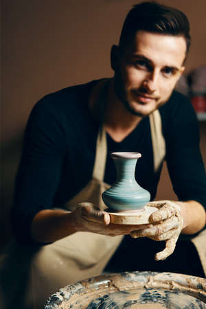 Smiling handsome man showing handmade ceramic pot at pottery workshop. Art concept Imagens