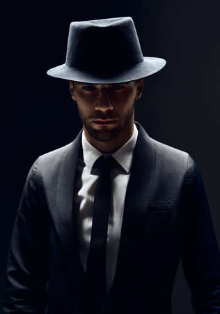Handsome confident man in black suit and hat on dark background. Man beauty concept