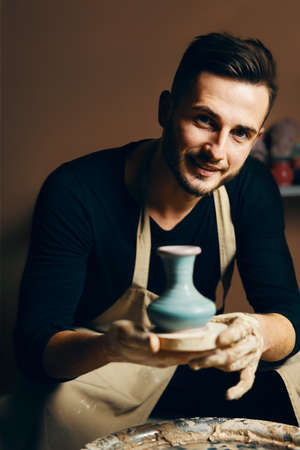 Smiling handsome man showing handmade ceramic pot at pottery workshop. Art concept Stockfoto