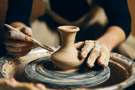 Mann-Töpfer, der an der Töpferscheibe arbeitet, die Keramiktopf aus Ton in der Töpferwerkstatt herstellt. Kunstkonzept