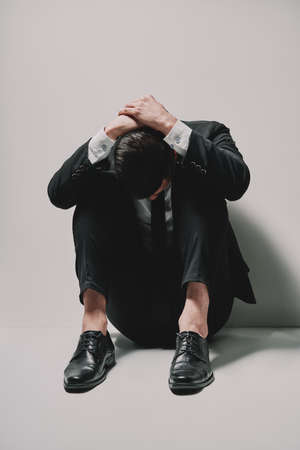 Depressed business man sitting on floor head in hands on white background. problems and  dramatic concept