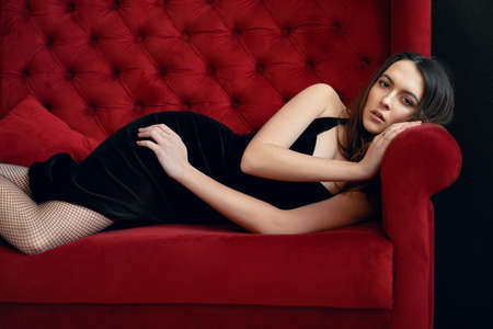 Portrait of sensual beautiful woman posing in sexy black dress on red sofa. Female beauty concept Imagens