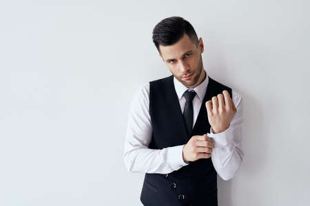 Handsome young man adjusting his sleeves and fixing his cufflinks