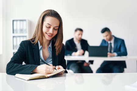 Beautiful smiling business woman writing and making notes in notebook in modern office