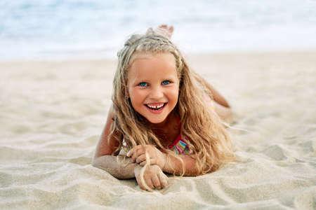 Adorable little blonde girl relax on sandy beach enjoy sea