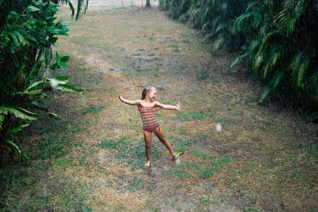 Pretty little girl enjoy the rain and dancing on the street under rainfall in summer Stockfoto