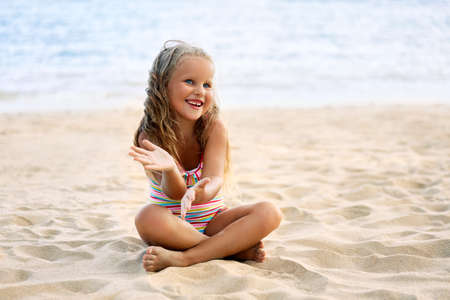 Happy cute child playing on sandy beach.