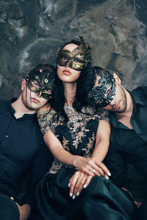 Beautiful young woman and two men in mysterious black mask sitting on floor in studio Stockfoto