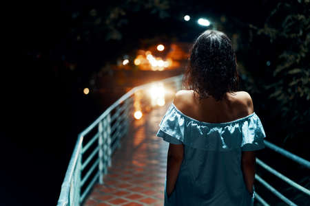 Young lonely woman walking on the bridge at night Stock fotó