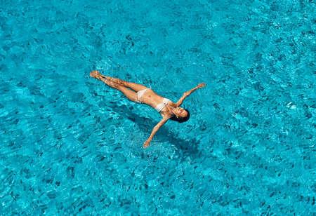 La vista dall'alto della giovane donna magra in bikini bianco si rilassa e galleggia nella piscina a sfioro