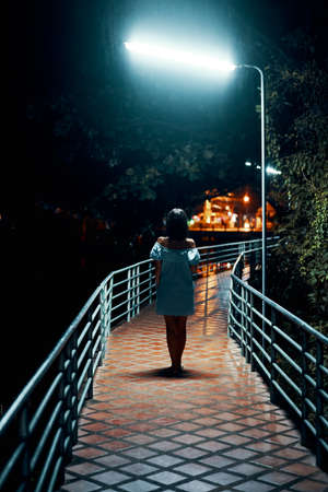 Young lonely woman walking on the bridge at night