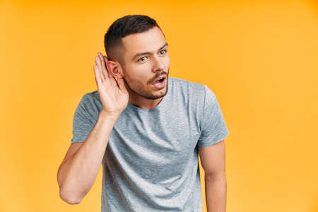 Young surprised man listening something carefully and holds his hand near ear over yellow background