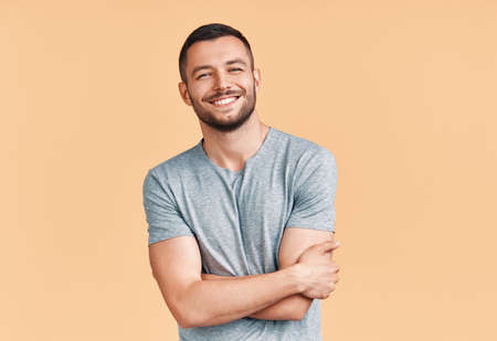 Happy smiling handsome man with crossed arms looking to camera over beige background Фото со стока