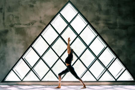 Young beautiful woman doing yoga asana Warrior I Pose on large triangular window background
