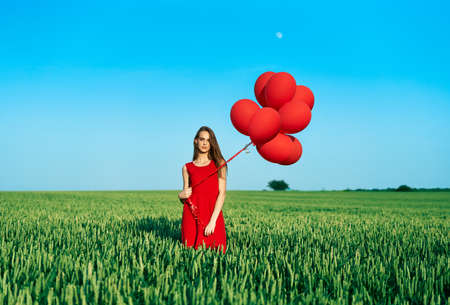 Young beautiful woman in red dress posing in green field with red balloons Archivio Fotografico
