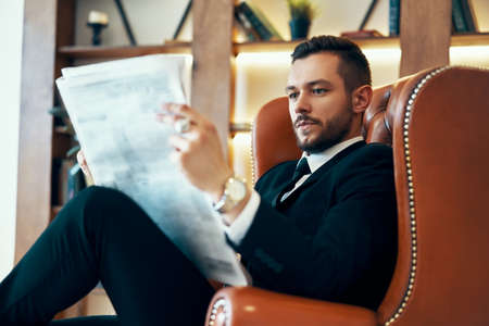 Confident young businessman reading newspaper and latest news while sitting in armchair Imagens - 133374440