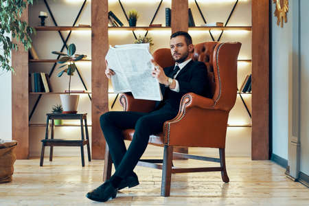Confident young businessman reading newspaper and latest news while sitting in armchair Imagens - 133374450