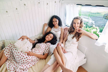 Smiling multi ethnic girls have fun together and enjoy home party inside the camper van.